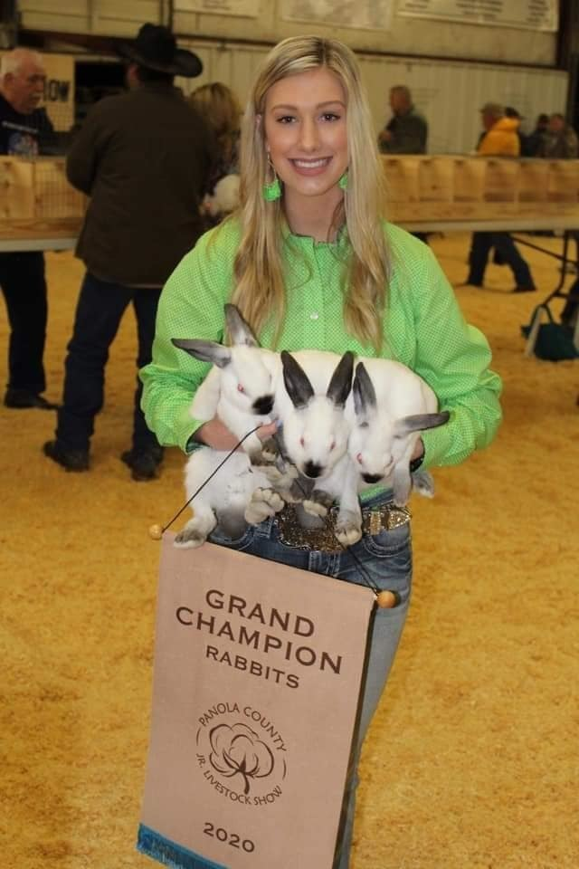 Macie Kate Harris holding her three show rabbits